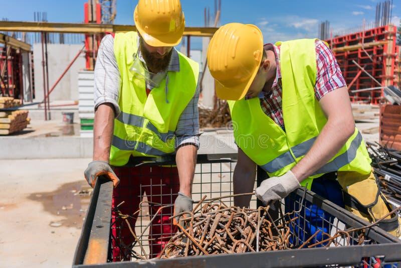 Δύο εργαζόμενοι που ελέγχουν έναν σωρό των σκουριασμένων φραγμών χάλυβα κατά τη διάρκεια της εργασίας στο τ στοκ φωτογραφίες με δικαίωμα ελεύθερης χρήσης