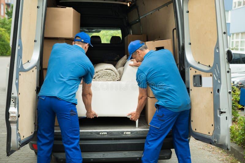 Δύο εργαζόμενοι που ρυθμίζουν τον καναπέ στο φορτηγό στοκ φωτογραφία με δικαίωμα ελεύθερης χρήσης