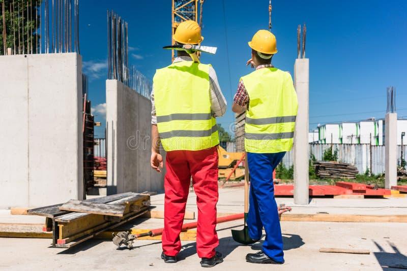 Δύο εργαζόμενοι που φορούν τον εξοπλισμό ασφάλειας προγραμματίζοντας την εργασία στοκ εικόνες