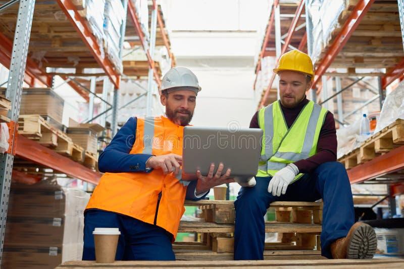 Δύο εργαζόμενοι που χρησιμοποιούν το lap-top στην αποθήκη εμπορευμάτων στοκ φωτογραφίες