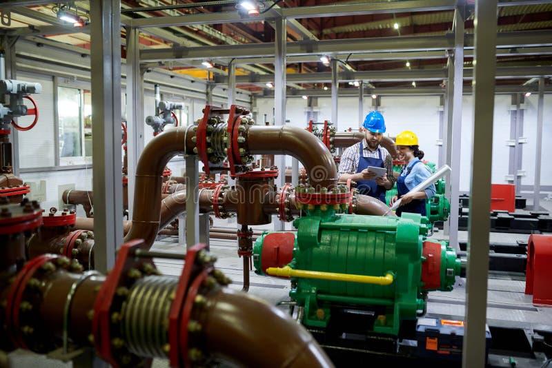 Δύο εργαζόμενοι στο σύστημα καθαρισμού νερού στοκ φωτογραφίες