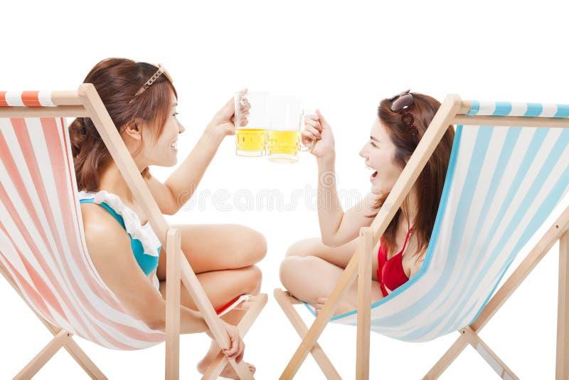 Δύο ευθυμίες μπύρας εκμετάλλευσης κοριτσιών ηλιοφάνειας σε μια καρέκλα παραλιών στοκ εικόνα