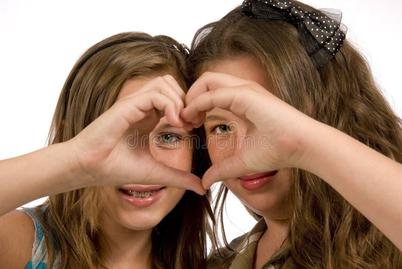 Τα ευτυχή κορίτσια παρουσιάζουν αδερφικά αγάπη που απομονώνεται στοκ εικόνες