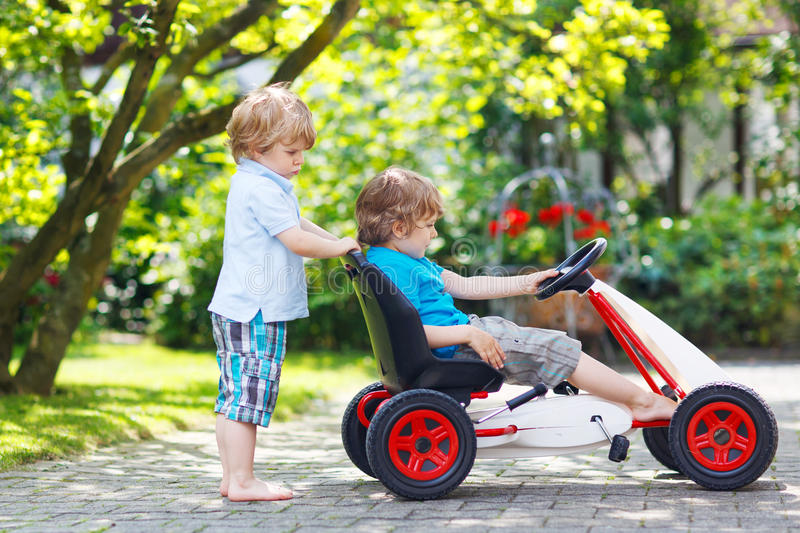 Δύο ευτυχή αγόρια αμφιθαλών που παίζουν με το αυτοκίνητο παιχνιδιών στοκ φωτογραφία με δικαίωμα ελεύθερης χρήσης