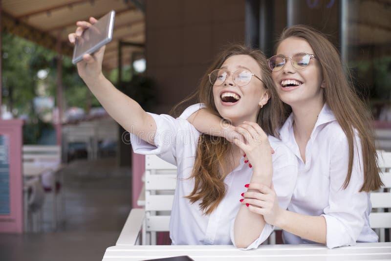 Δύο ευτυχή κορίτσια που κάνουν ένα selfie στο θερινό καφέ στοκ φωτογραφία με δικαίωμα ελεύθερης χρήσης