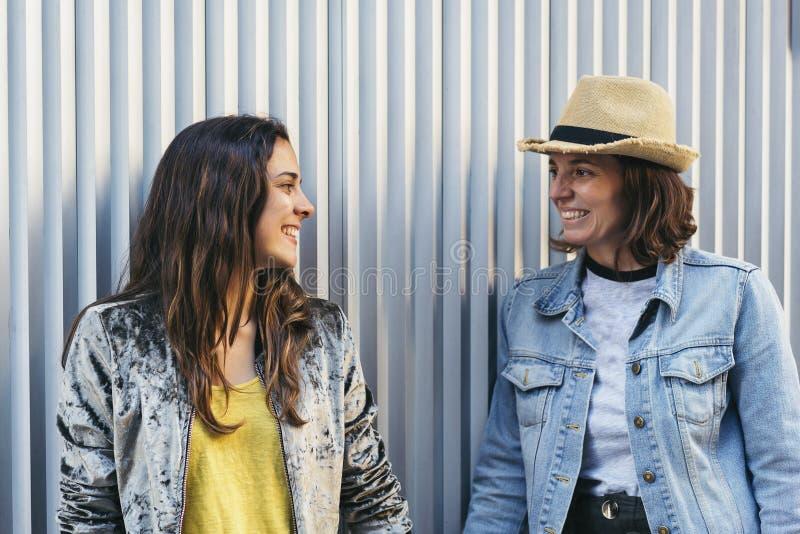 Δύο ευτυχή κορίτσια που φαίνονται μεταξύ τους και που χαμογελούν στο μεταλλικό και καθαρό υπόβαθρο στοκ φωτογραφία με δικαίωμα ελεύθερης χρήσης