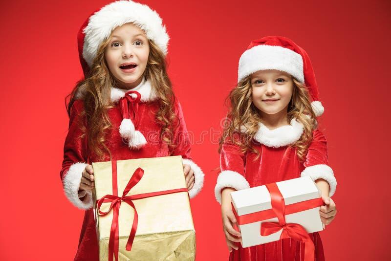 Δύο ευτυχή κορίτσια στα καπέλα Άγιου Βασίλη με τα κιβώτια δώρων στο στούντιο στοκ φωτογραφία