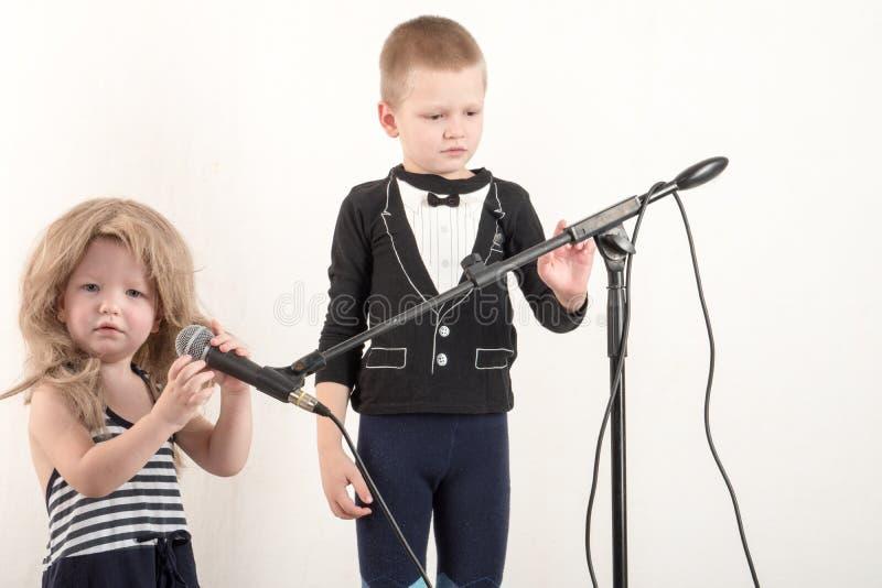 Δύο ευτυχή μικρά παιδιά στα έξυπνα ενδύματα τραγουδούν ένα τραγούδι με ένα μικρόφωνο στο σπίτι Να προετοιμαστεί για το καραόκε Χρ στοκ εικόνες
