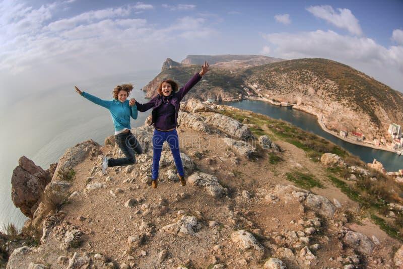 Δύο ευτυχή νέα κορίτσια γυναικών που πηδούν σε ένα βουνό που αγνοεί το θόριο στοκ φωτογραφίες