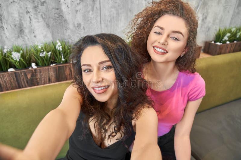 Δύο ευτυχή νέα κορίτσια που κάνουν selfie από κοινού στοκ εικόνα