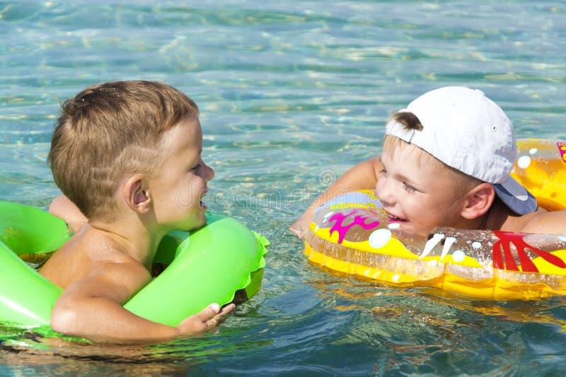Δύο ευτυχή παιδιά που έχουν τη διασκέδαση στο νερό με το inflateble δαχτυλίδι στοκ εικόνες