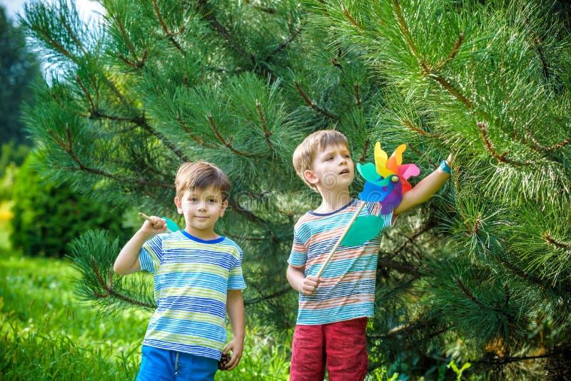 Δύο ευτυχή παιδιά που παίζουν στον κήπο με τον ανεμόμυλο pinwheel Οι λατρευτοί αδελφοί αμφιθαλών είναι καλύτεροι φίλοι Χαριτωμένο στοκ φωτογραφίες