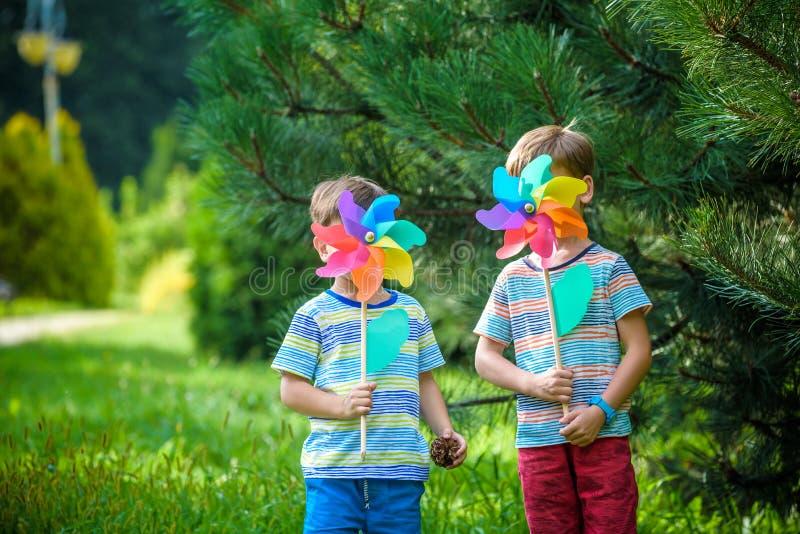 Δύο ευτυχή παιδιά που παίζουν στον κήπο με τον ανεμόμυλο pinwheel πλίθας στοκ φωτογραφίες