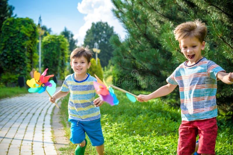 Δύο ευτυχή παιδιά που παίζουν στον κήπο με τον ανεμόμυλο pinwheel πλίθας στοκ φωτογραφία με δικαίωμα ελεύθερης χρήσης