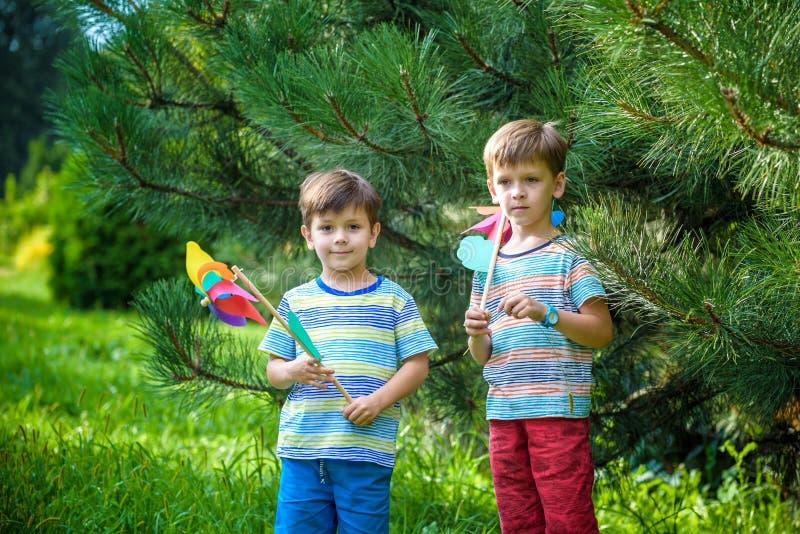 Δύο ευτυχή παιδιά που παίζουν στον κήπο με τον ανεμόμυλο pinwheel πλίθας στοκ εικόνες με δικαίωμα ελεύθερης χρήσης