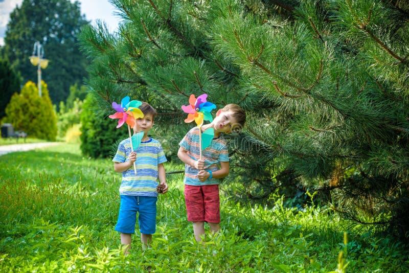 Δύο ευτυχή παιδιά που παίζουν στον κήπο με τον ανεμόμυλο pinwheel πλίθας στοκ φωτογραφία