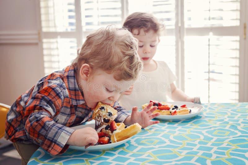Δύο ευτυχή παιδιά ζευγαρώνουν το κορίτσι αγοριών που τρώει τις βάφλες προγευμάτων με τα φρούτα καθμένος στον πίνακα στοκ εικόνα με δικαίωμα ελεύθερης χρήσης