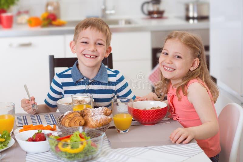 Δύο ευτυχή παιδιά που έχουν το πρόγευμα στην κουζίνα στοκ φωτογραφία με δικαίωμα ελεύθερης χρήσης