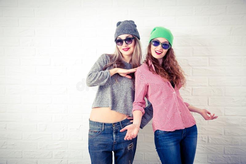 Δύο ευτυχή χαμογελώντας κορίτσια Hipster στον άσπρο τοίχο στοκ εικόνα