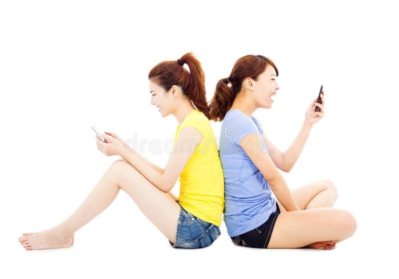 Δύο ευτυχή όμορφα κορίτσια που παίζουν το έξυπνο τηλέφωνο στοκ εικόνα