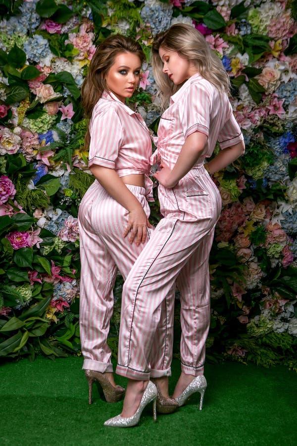 Δύο ευτυχή όμορφα blondes στις προκλητικές ριγωτές πυτζάμες και τακούνια σε ένα υπόβαθρο λουλουδιών Στέκονται κοντά στοκ φωτογραφίες