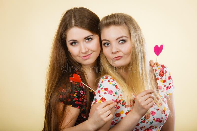 Δύο ευτυχείς γυναίκες που κρατούν την καρδιά στο ραβδί στοκ εικόνες