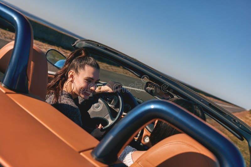 Δύο ευτυχείς γυναίκες στο καμπριολέ που οδηγεί και που έχει τη διασκέδαση απομονωμένο οπισθοσκόπο λευκό στοκ φωτογραφία