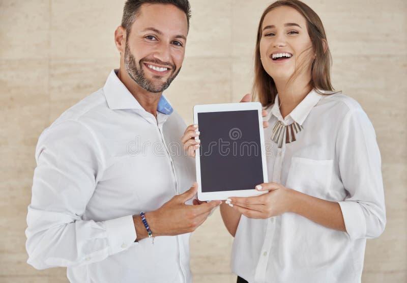 Δύο ευτυχείς επιχειρηματίες που κρατούν την ολοκαίνουργια ταμπλέτα στοκ εικόνα με δικαίωμα ελεύθερης χρήσης