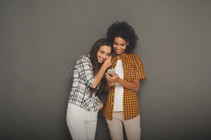Δύο ευτυχείς θηλυκοί φίλοι που χρησιμοποιούν το smartphone στοκ εικόνα