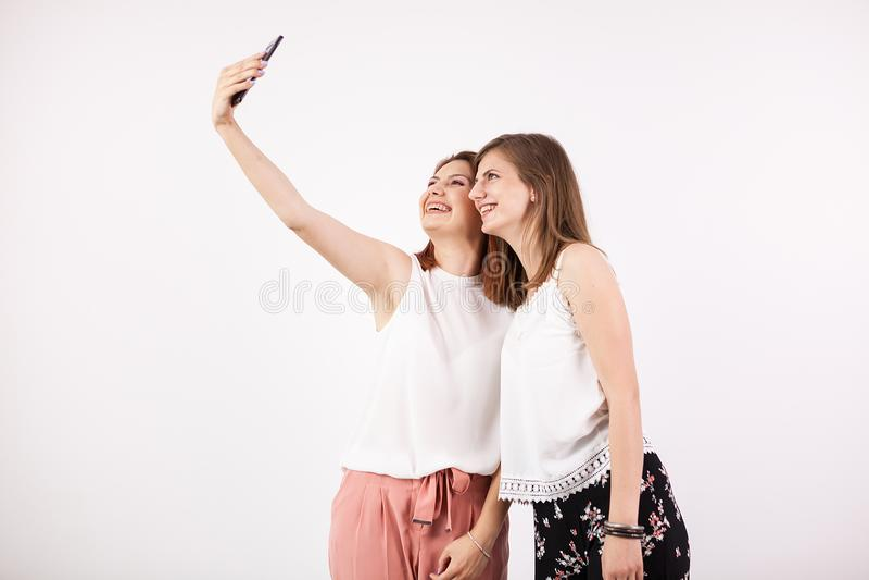 Δύο ευτυχείς πανέμορφοι νέοι φίλοι γυναικών που χαμογελούν και που παίρνουν ένα selfie στοκ εικόνα