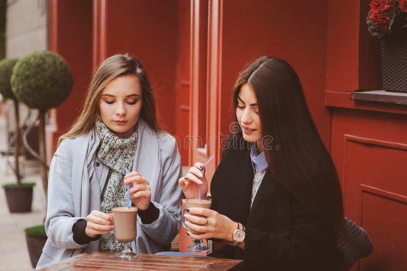 Δύο ευτυχείς φίλοι κοριτσιών που μιλούν και που πίνουν τον καφέ στην πόλη φθινοπώρου στον καφέ στοκ εικόνες με δικαίωμα ελεύθερης χρήσης