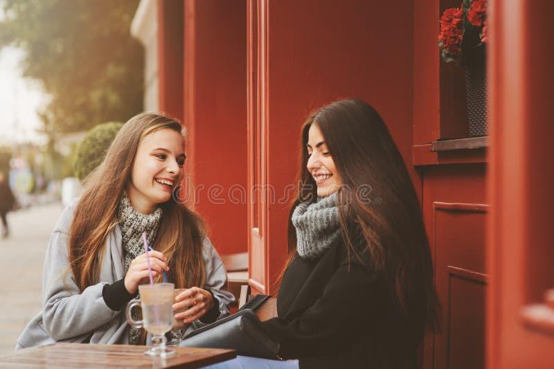 Δύο ευτυχείς φίλοι κοριτσιών που μιλούν και που πίνουν τον καφέ στην πόλη φθινοπώρου στον καφέ στοκ φωτογραφία