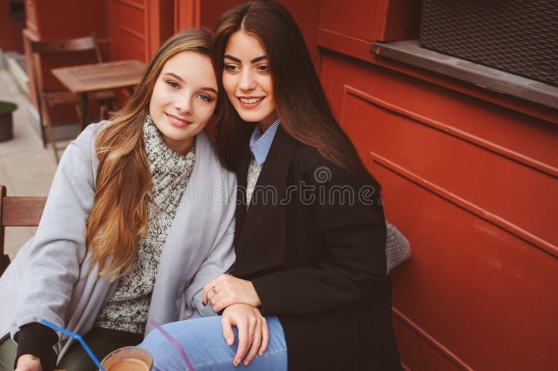 Δύο ευτυχείς φίλοι κοριτσιών που μιλούν και που πίνουν τον καφέ στην πόλη φθινοπώρου στον καφέ στοκ φωτογραφίες