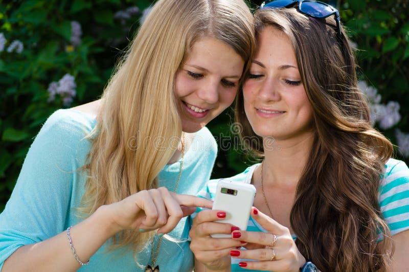 Δύο ευτυχείς φίλοι κοριτσιών εφήβων και κινητό τηλέφωνο στοκ φωτογραφία