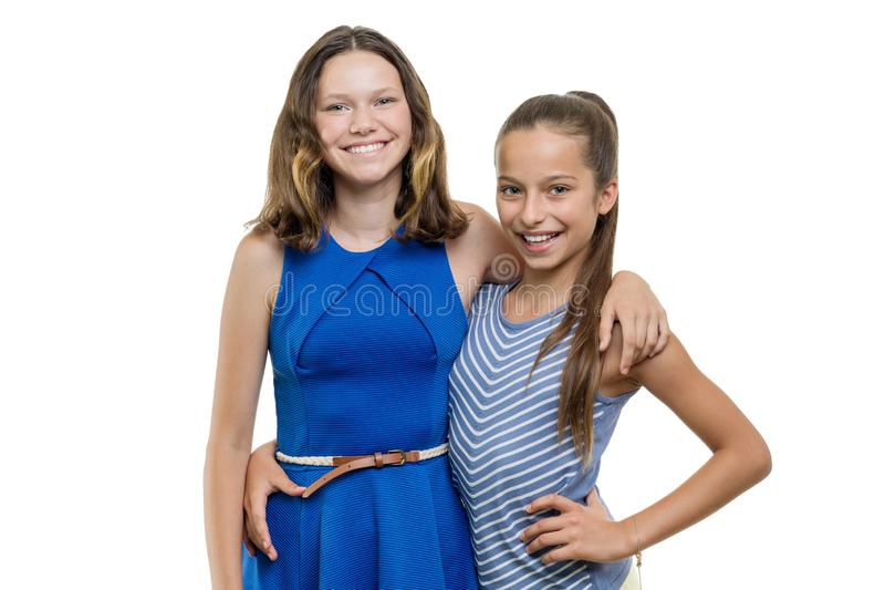 Δύο ευτυχείς όμορφοι φίλοι νέων κοριτσιών που αγκαλιάζουν, με το τέλειο άσπρο χαμόγελο, που απομονώνεται στο άσπρο υπόβαθρο στοκ φωτογραφίες