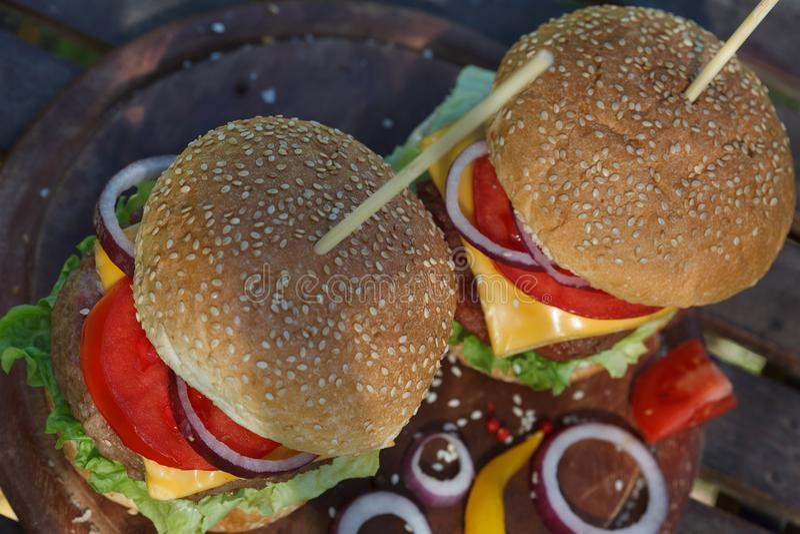 Δύο εύγευστα burgers στον ξύλινο πίνακα στοκ εικόνα