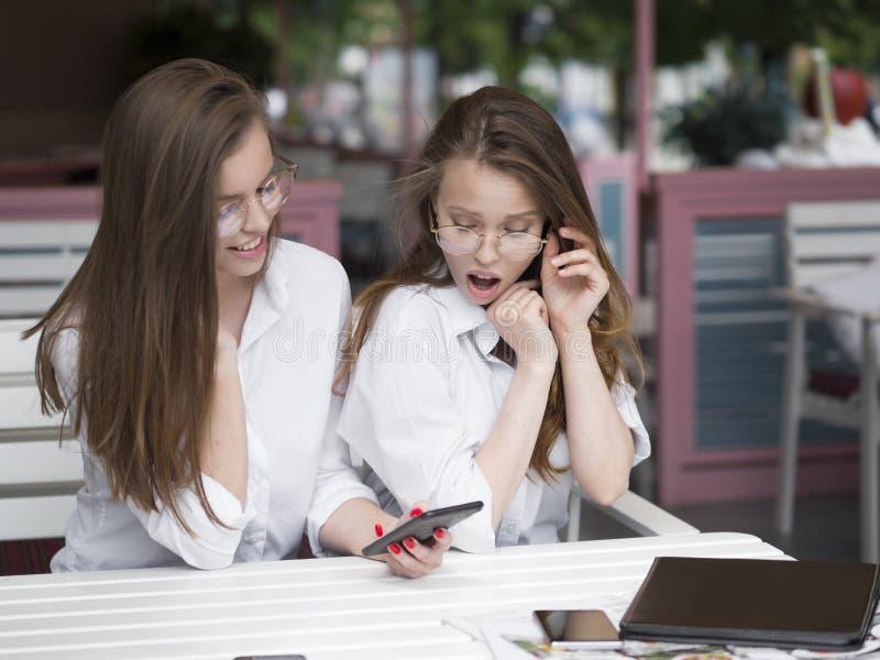 Δύο εύθυμα και όμορφα κορίτσια κάθονται μαζί σε έναν καφέ και προσέχουν κάτι στο τηλέφωνο στοκ εικόνα