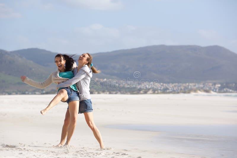 Δύο εύθυμες φίλες που περνούν καλά στην παραλία στοκ εικόνες