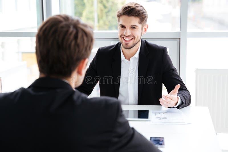Δύο εύθυμοι επιχειρηματίες χρησιμοποιώντας την ταμπλέτα και εργαζόμενος στην επιχειρησιακή συνεδρίαση στοκ φωτογραφία
