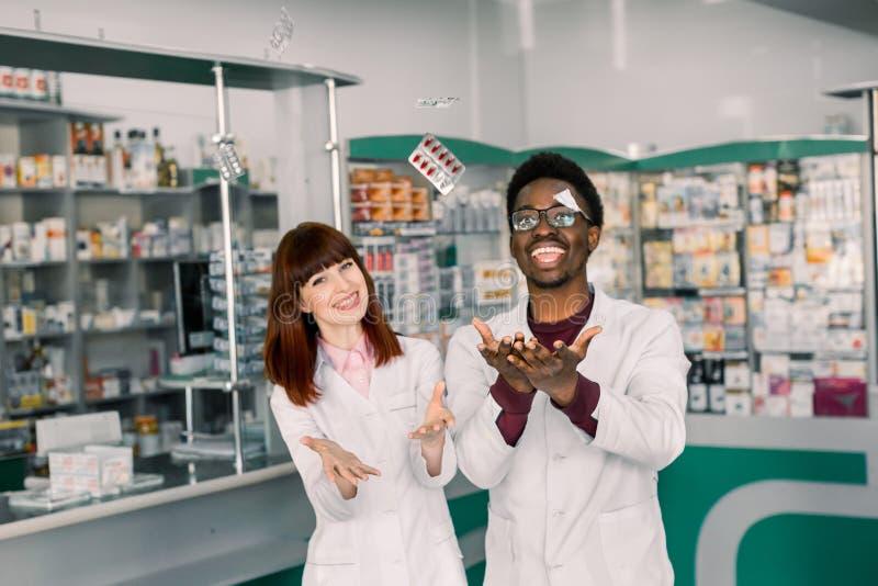 Δύο εύθυμος multiethnical φαρμακοποιοί, άνδρας και γυναίκα που απασχολούνται μαζί και που έχουν στη διασκέδαση, που ρίχνει επάνω  στοκ εικόνες με δικαίωμα ελεύθερης χρήσης