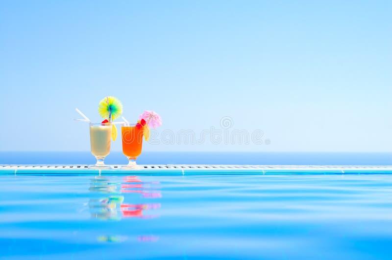 Δύο ζωηρόχρωμα τροπικά κοκτέιλ κοντά στην πισίνα στο υπόβαθρο της θερμής μπλε θάλασσας Εξωτικές θερινές διακοπές στοκ εικόνες