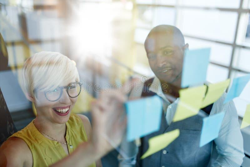Δύο δημιουργικοί millenial μικροί ιδιοκτήτες επιχείρησης που εργάζονται στο κοινωνικό 'brainstorming' στρατηγικής μέσων που χρησι στοκ φωτογραφία με δικαίωμα ελεύθερης χρήσης