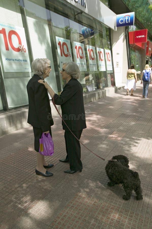 Δύο ηλικιωμένες γυναίκες σταματούν για μια στιγμή της συζήτησης στις οδούς της Μαδρίτης, Ισπανία στοκ εικόνες