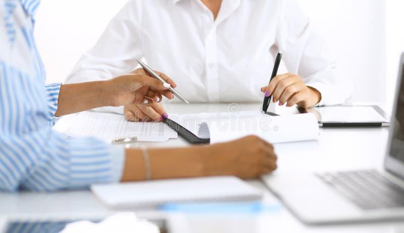 Δύο θηλυκοί λογιστές που ελέγχουν τη οικονομική κατάσταση ή που μετρούν από το εισόδημα υπολογιστών για τη φορολογική μορφή, χέρι στοκ εικόνες