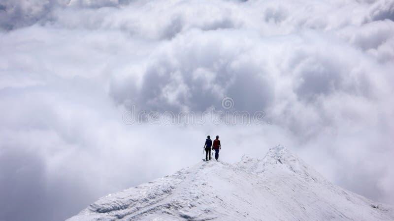 Δύο θηλυκοί ορειβάτες βουνών σε μια στενή κορυφογραμμή κορυφών υψηλή επάνω από τις τράπεζες σύννεφων στις κοιλάδες κατωτέρω στοκ φωτογραφίες