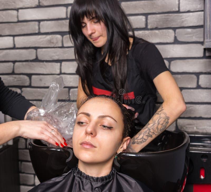 Δύο θηλυκοί στιλίστες παίρνουν smock στη γυναίκα μετά από να πλύνουν το χ της στοκ εικόνα με δικαίωμα ελεύθερης χρήσης
