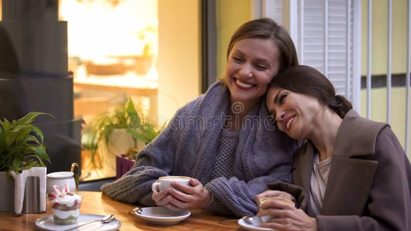 Δύο θηλυκοί φίλοι που έχουν την καλή χρονική συνεδρίαση στον καφέ, τον καφέ και το επιδόρπιο στον πίνακα στοκ φωτογραφίες