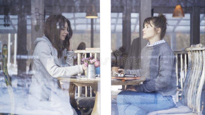 Δύο θηλυκοί φίλοι που συναντιούνται σε έναν καφέ για να μιλήσει στοκ φωτογραφία με δικαίωμα ελεύθερης χρήσης