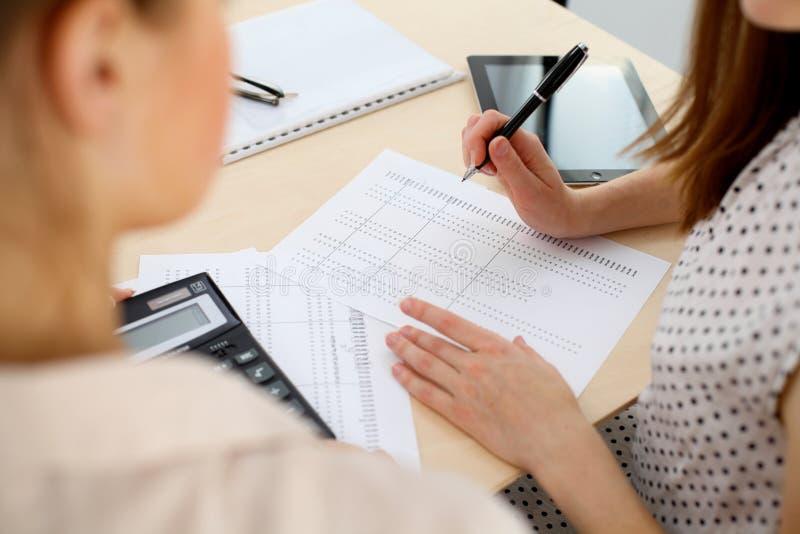 Δύο θηλυκοί λογιστές που βασίζονται στο εισόδημα υπολογιστών για την κινηματογράφηση σε πρώτο πλάνο χεριών ολοκλήρωσης φορολογική στοκ εικόνα με δικαίωμα ελεύθερης χρήσης