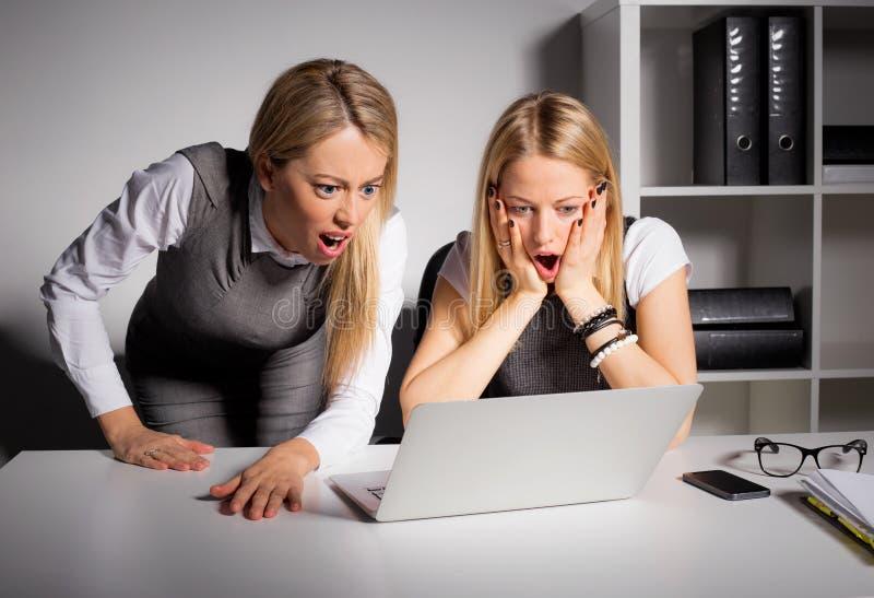 Δύο θηλυκοί συνάδελφοι που εξετάζουν τον υπολογιστή στη δυσπιστία στοκ εικόνα με δικαίωμα ελεύθερης χρήσης